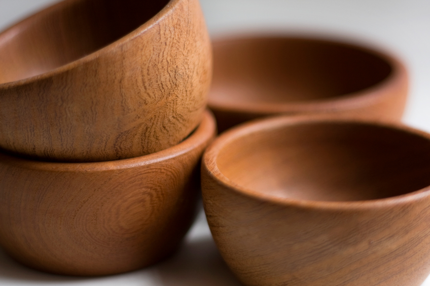 A DSLR photo close up studio shot of 4 wooden bowls handmade. There is a pile of two at the left side and one behind the other on the right side.